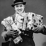 Man with coat, gloves and hat carrying Christmas gifts