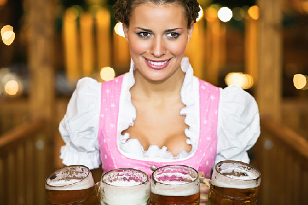 Waitress holding 4 Mass beer jugs at Oktoberfest,