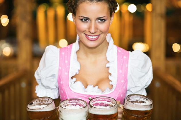 Waitress holding 4 Mass beer jugs at Oktoberfest,